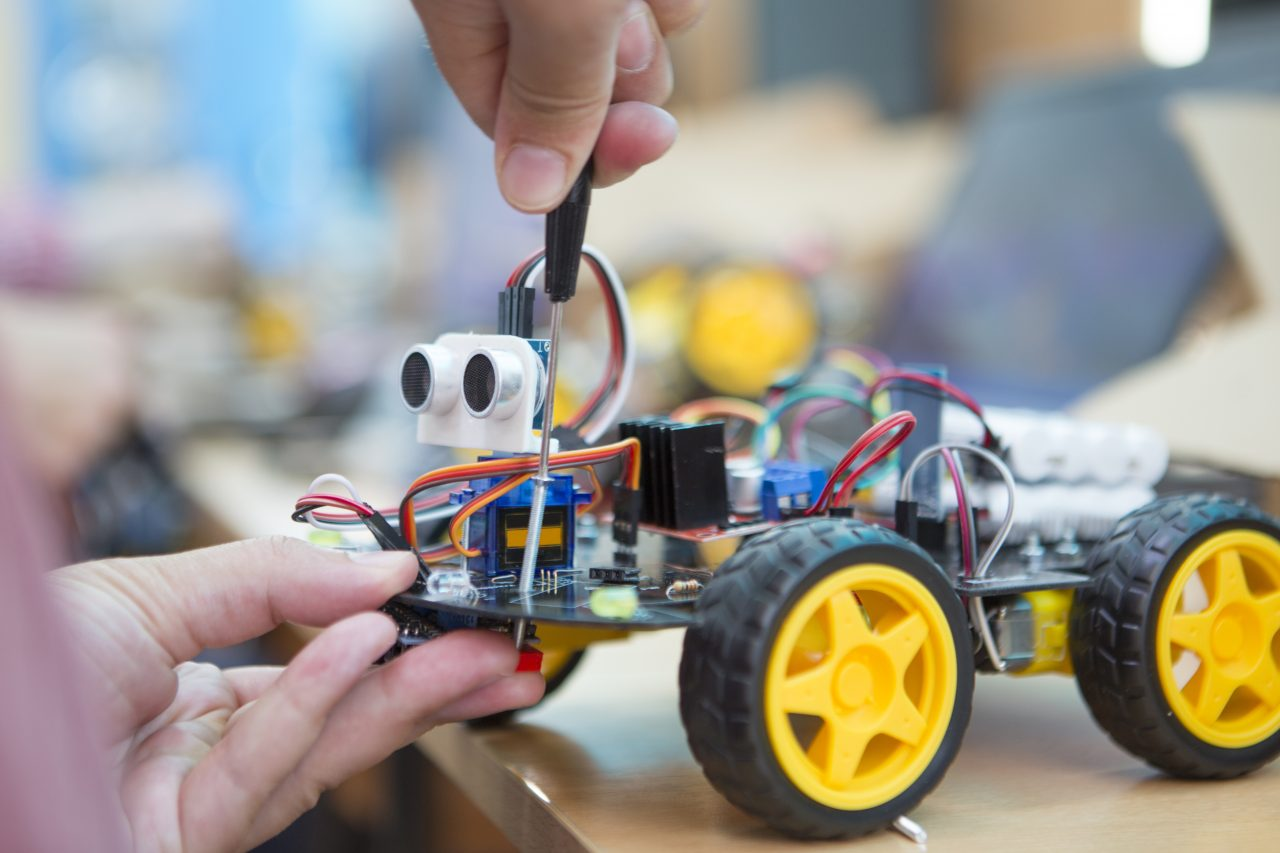 student doing robot with screwdriver in robotics coding class